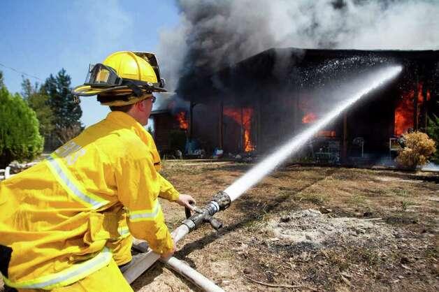 Jason Birdwell, of the Ferris Fire Department, hoses down a home in  Jefferson. Photo: Adam Sacasa, Associated Press / Texarkana Gazette