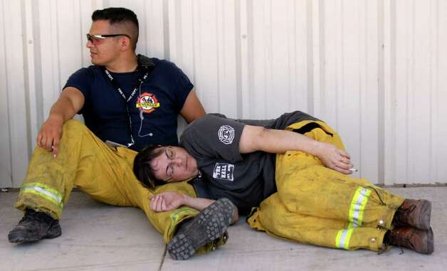 EFFECTS OF THE BLAZE: Wildfire evacuees David Gabrile, above left, and his wife, MaryAnn, find out Sunday they will not yet be allowed to return to their home during a meeting at Waller High School in Waller. In Magnolia, Joey Martinez, left, and Tara Johnson of the Riverside Volunteer Fire Department grab some rest Sunday after fighting fires overnight. Photo: Melissa Phillip / © 2011 Houston Chronicle