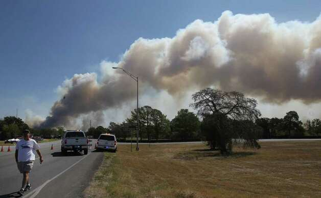 A plume of smoke billows across the sky at a roadblock near Bastrop State Park  as wildfires continue to burn in the area. (Monday September 5, 2011) JOHN DAVENPORT/jdavenport@express-news.net Photo: JOHN DAVENPORT, SAN ANTONIO EXPRESS-NEWS / SAN ANTONIO EXPRESS-NEWS (Photo can be sold to the public)