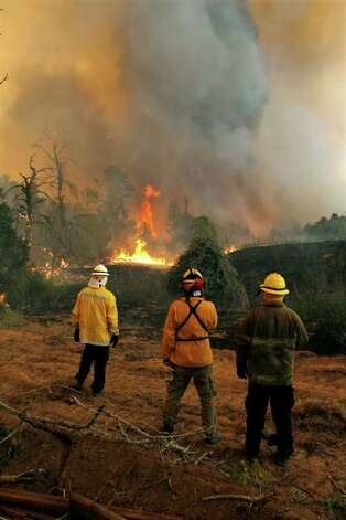 Firefighters from around the state battle a large wildfire on Highway 71 near Smithville, Texas, Monday, Sep. 5, 2011.  A roaring wildfire raced unchecked Monday through rain-starved farm and ranchland in Texas, destroying nearly 500 homes during a rapid advance fanned in part by howling winds from the remnants of Tropical Storm Lee.  (AP Photo/Erich Schlegel) Photo: Erich Schlegel, Associated Press / FR 62355 AP