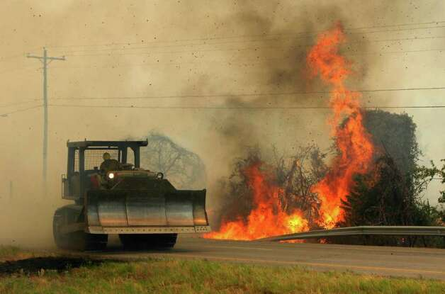 A large wildfire burns along Highway 71 near Smithville, Texas  as a bulldozer from the Texas Forest Service rumbles by Monday, Sep. 5, 2011.  A roaring wildfire raced unchecked Monday through rain-starved farm and ranchland in Texas, destroying nearly 500 homes during a rapid advance fanned in part by howling winds from the remnants of Tropical Storm Lee.  (AP Photo/Erich Schlegel) Photo: Erich Schlegel, Associated Press / FR 62355 AP