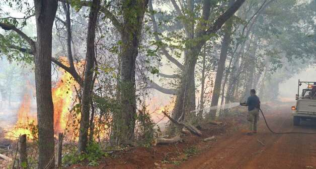 A member of the Cushing V.F.D. fights a brush fire that started when a car caught fire Monday, Sept. 5, 2011 in Nacogdoches, Texas.  One person was injured in a possible tornado in Cherokee County as the remnants of Tropical Storm Lee crossed the state Monday afternoon, authorities said.  Lt. Jay Baker with the Cherokee County Sheriff's department said the storm toppled trees, snapped power lines and damaged homes near Woodstock. He said the victim was taken to the hospital but the person's condition was not known.     (AP Photo/ Daily Sentinel, Dustin Anderson ) Photo: Dustin Anderson, Associated Press / Dustin Anderson:)