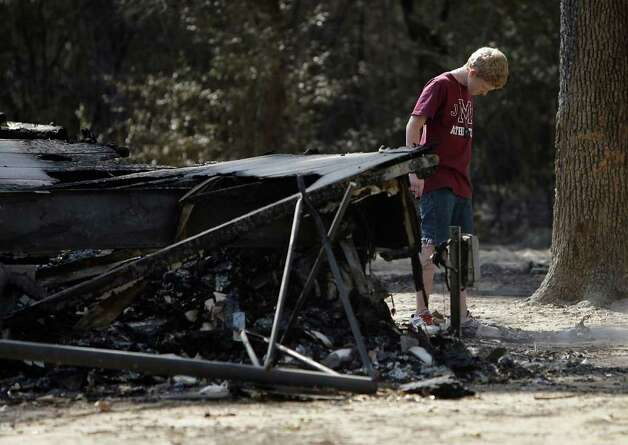 "Eli Fourniquet, 11, kicks dust around the outside of what is left of his family's mobile home in the River Park Country in Ranch Crest subdivision in Magnolia, after a fire ripped through the area, the residents were allowed to get back in yesterday. The owner, Amanda Fourniquet, was able to get out the valuables including photos and said, ""Other than that, it's all replaceable."" Photo: Karen Warren, Houston Chronicle / © 2011 Houston Chronicle"