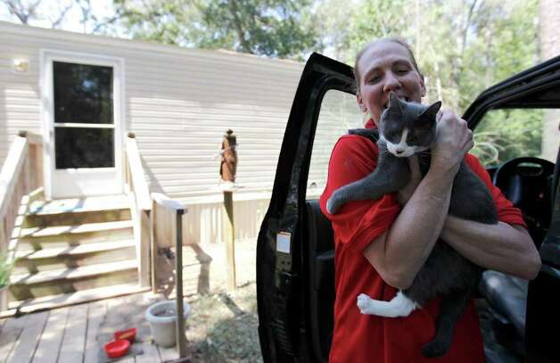 "Julie Offill carries her cat Charley into the house as she and her husband, Barry, return to their home in the Brenda Lane subdivision in Magnolia which had been under a mandatory evacuation order since Thursday.  The couple had sought shelter in the Wildwood United Methodist church on FM 1488. ""Hallellujah!"" said Julie after she drove onto the street and saw her house still standing with no evidence of fire around the neighborhood. ""Nobody knew if their house was still standing!"" Photo: Karen Warren, Houston Chronicle / © 2011 Houston Chronicle"