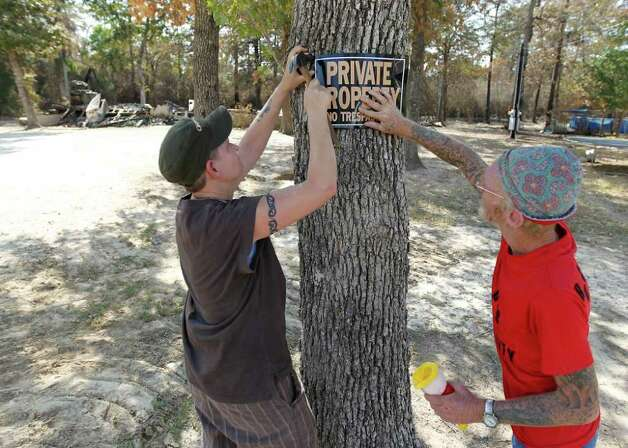 "Sandy Duell, left, and her neighbor Philip Pingilley put up a ""No Trespassing"" sign on a tree in front their neighbor's mobile home that was reduced to ashes in the River Park Country in Ranch Crest subdivision in Magnolia, Monday, Sept. 12, 2011, after a fire ripped through the area, the residents were allowed to get back in yesterday. The owner Amanda Fourniquet was able to get out the valuables including photos and said, ""Other than that, it's all replaceable."" Photo: Karen Warren, Houston Chronicle / © 2011 Houston Chronicle"