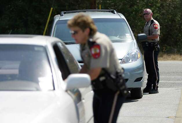 Montgomery County Sheriff deputies  Rick Ashmore and Donna Rippley stop cars entering FM 1486 off of FM1488, Monday, Sept. 12, 2011, as they check IDs for residents that were allowed to reenter the area after a mandatory evacuation due to fires in the area. Photo: Karen Warren, Houston Chronicle / © 2011 Houston Chronicle