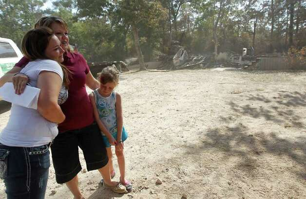 "Amanda Fourniquet, center, hugs her cousin Courtney Conklin, and her daughter, Eve Fourniquet, 7, in front of what is left of their mobile home in the River Park Country in Ranch Crest subdivision in Magnolia, Monday, Sept. 12, 2011, after a fire ripped through the area, the residents were allowed to get back in yesterday. Fourniquet was able to get out the valuables including photos and said, ""Other than that, it's all replaceable."" Photo: Karen Warren, Houston Chronicle / © 2011 Houston Chronicle"