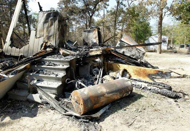 "A mobile home sits in ashes in the River Park Country in Ranch Crest subdivision in Magnolia, Monday, Sept. 12, 2011, after a fire ripped through the area, the residents were allowed to get back in yesterday. The owner Amanda Fourniquet was able to get out the valuables including photos and said, ""Other than that, it's all replaceable."" Photo: Karen Warren, Houston Chronicle / © 2011 Houston Chronicle"