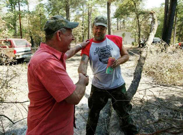 Alvin Becker thanks his neighbor Randy Stack for saving his home upon returning to their home in Circle D Estates after the wildfires near Bastrop, Texas, Monday September 12, 2011. Their home and three others next to it were the only one still standing Monday, thanks to the efforts of their neighbor Randy Stack who stayed behind and used garden hoses to keep the flames down all week. Officials are saying approximately 1,500 homes have been destroyed making this the worst wildfire disaster in Texas history.  (Erich Schlegel/Special Contributor) Photo: Erich Schlegel, Houston Chronicle / ©2011 Erich Schlegel