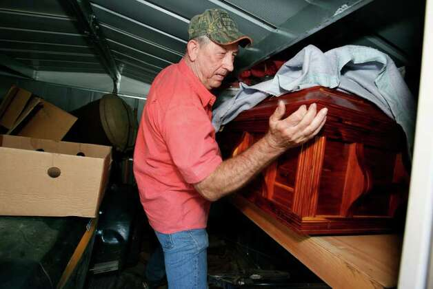 Alvin Becker examines the caskets he built for himself and his wife upon returning to their home in Circle D Estates after the wildfires near Bastrop, Texas, Monday September 12, 2011. Their home and three others next to it were the only one still standing Monday, thanks to the efforts of their neighbor Randy Stack who stayed behind and used garden hoses to keep the flames down all week. Officials are saying approximately 1,500 homes have been destroyed making this the worst wildfire disaster in Texas history.  (Erich Schlegel/Special Contributor) Photo: Erich Schlegel, Houston Chronicle / ©2011 Erich Schlegel