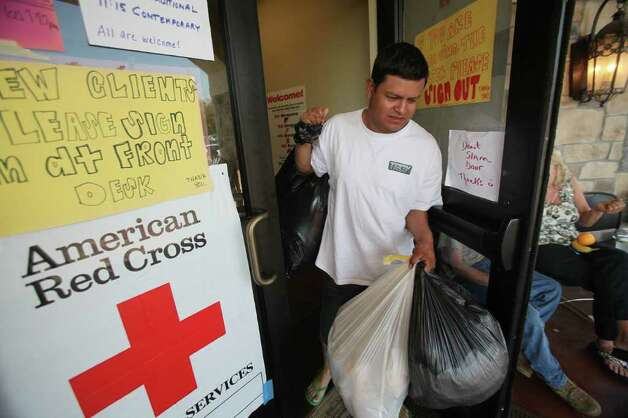 Victor Veloz carries bags of clothes and blankets to his vehicle at the Red Cross shelter at Wildwood United Methodist Church on Sunday, Sept. 11, 2011, in Magnolia.  Veloz and his family headed home after evacuation orders were lifted for his subdivision east of FM 1774 and north of Grimes County lines. Photo: Mayra Beltran, Houston Chronicle / © 2011 Houston Chronicle