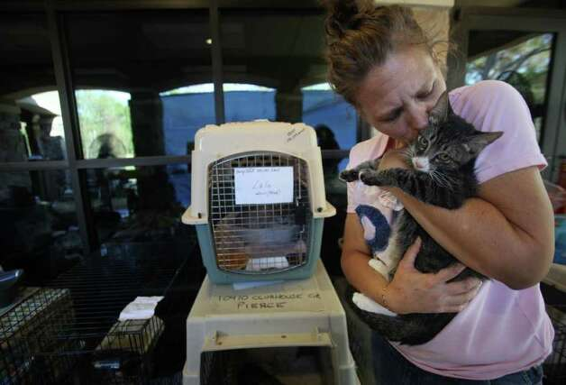 Michelle Johnson, of Magnolia, kisses her cat as she takes a break from helping to care for other resident's pets at the Red Cross Shelter located at Wildwood United Methodist Church on Sunday, Sept. 11, 2011, in Magnolia. Johnson lives in the backside of Ranch Crest and is still worried about her home. Photo: Mayra Beltran, Houston Chronicle / © 2011 Houston Chronicle