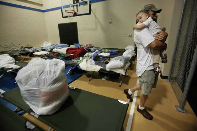 Jim Morgan, 46, embraces son Jared Morgan, 2, at the Red Cross Shelter located inside Wildwood United Methodist Church on Sunday, Sept. 11, 2011, in Magnolia. Morgan was celebrating his son's birthday when his family was asked to evacuate home along 1486 and Hall Dr. due to a nearby wildfire. They have evacuated three times since Monday. The Red Cross is still taking donations at the shelter. Photo: Mayra Beltran, Houston Chronicle / © 2011 Houston Chronicle