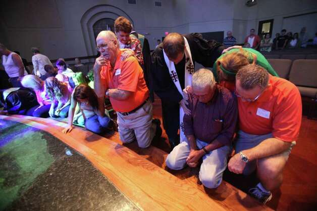 The congregation prays together during Sunday Service at Wildwood United Methodist Church as it observes the Sept. 11th attacks anniversary and pray for fire victims in the tri-county wildfires on Sunday, Sept. 11, 2011, in Magnolia. Photo: Mayra Beltran, Houston Chronicle / © 2011 Houston Chronicle