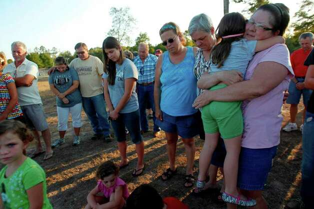 Kathy Kuhne embraces her daughter Starla Lopez, 4, at the Believers Fellowship gathering that offered prayers for fire victims in Magnolia.  About 70 people attended. Photo: Mayra Beltran, Houston Chronicle / © 2011 Houston Chronicle
