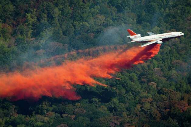 "DC-10 airplane drops retardant to help fight a large wildfire, Saturday, Sept. 10, 2011, near Magnolia, Texas. The plane,  a converted DC-10 jet is capable of dropping 12,000 gallons of fire retardant. was assigned to Bastrop County in Central Texas  but was temporarily diverted to attack a ""particularly aggressive fire"" that has been burning across Montgomery, Grimes and Waller counties, said Carman Apple, Texas Forest Service spokeswoman. Grimes County Sheriff Don Sowell said he hopes the use of the plane reinforces the bulldozers that had been working through the night to contain the active fire inside an earthen berm. Photo: Smiley N. Pool, Houston Chronicle / © 2011  Houston Chronicle"