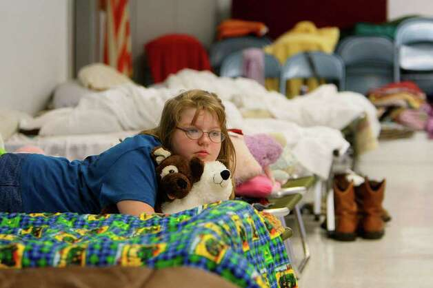 Brandy Collmorgen rests on her cot at the St. John's Lutheran Church shelter where evacuated families are staying due to wildfires on Saturday, Sept. 10, 2011 in Waller, TX. Harada evacuated from the Field Store area in Waller County, and believes her home is untouched by fire. (Mayra Beltran / Houston Chronicle) Photo: Mayra Beltran, Houston Chronicle / © 2011 Houston Chronicle