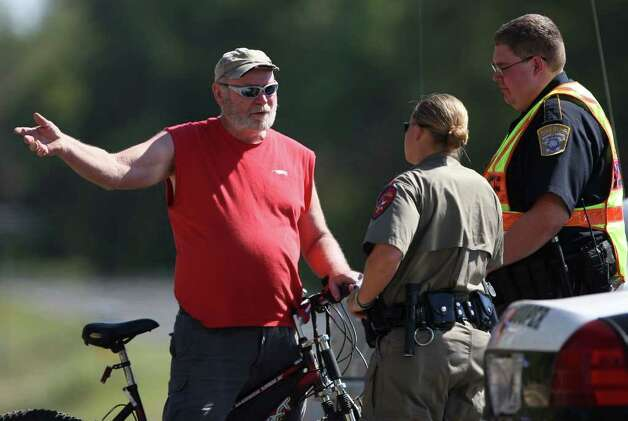 "A man who would only identify himself as ""Public Enemy #1, Because I'm a Christian"" talks with state Trooper A. Zandt, center, and Brazos County Officer Nathan Dennis at a FM 1774 roadblock.  Photo: Eric Christian Smith, For The Chronicle"