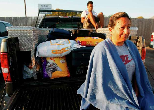 Oak Hallow resident Alba Edwards waits in the parking lot of the Field Store on FM 1488 as she waits for evacuation orders to be lifted and finally go home on Saturday, Sept. 10, 2011, in Waller County. Photo: Mayra Beltran, Houston Chronicle / © 2011 Houston Chronicle