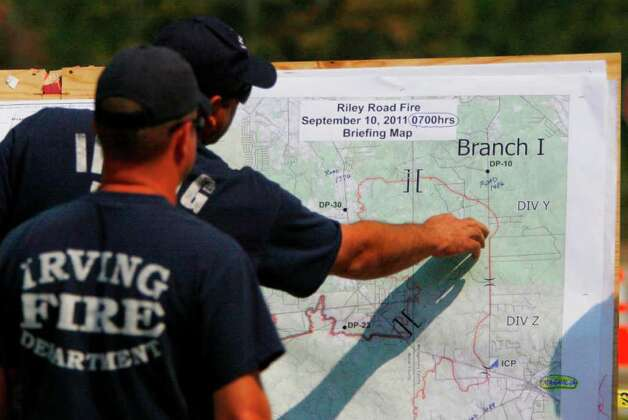 Members of the Irving Fire Department view the Riley Road fire briefing map at the unified command center as the tri-county fire continues to burn on Saturday, Sept. 10, 2011, in Magnolia. (Mayra Beltran / Houston Chronicle) Photo: Mayra Beltran, Houston Chronicle / © 2011 Houston Chronicle