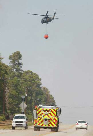 Black hawks carry water to a fire line near Magnolia as emergency crews move resources along FM 1774. Photo: Mayra Beltran, Houston Chronicle / © 2011 Houston Chronicle