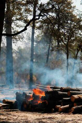 Flare up on a property where a home is destroyed by wildfire along FM 1774 where firefighters continue to battle the tri-county fire on Saturday, Sept. 10, 2011, in Magnolia. (Mayra Beltran / Houston Chronicle) Photo: Mayra Beltran, Houston Chronicle / © 2011 Houston Chronicle