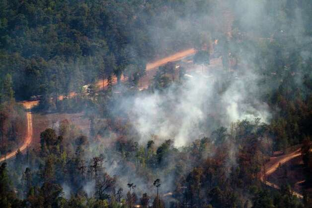 Smoke rises from a large wildfire, Saturday, Sept. 10, 2011, near Magnolia, Texas. Photo: Smiley N. Pool, Houston Chronicle / © 2011  Houston Chronicle