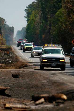 Emergency personnel drive through FM 1774 where firefighters continue to battle the tri-county wildfire on Saturday, Sept. 10, 2011, in Magnolia.(Mayra Beltran / Houston Chronicle) Photo: Mayra Beltran, Houston Chronicle / © 2011 Houston Chronicle
