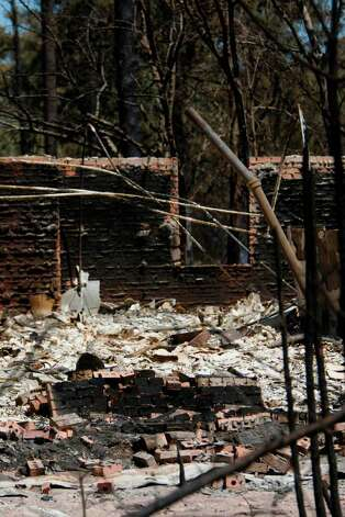Home destroyed by wildfire along FM 1774 where firefighters continue to battle the tri-county wildfire on Saturday, Sept. 10, 2011, in Magnolia. (Mayra Beltran / Houston Chronicle) Photo: Mayra Beltran, Houston Chronicle / © 2011 Houston Chronicle