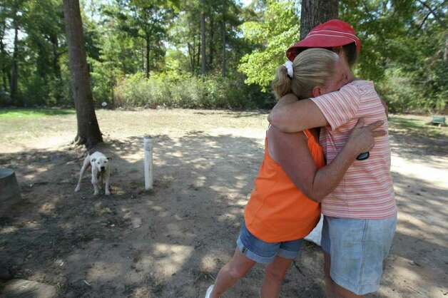 "Jackie Burgess, right, hugs friend Cathy Rash near FM 1774 in Plantersville on Saturday. The two have not been able to get back to their homes because of forced evacuations since Monday due to heavy smoke and wildfires in Grimes County. ""I evacuated with thirty-four cents,"" Burgess said. (Eric Christian