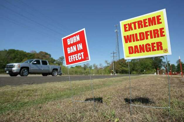 A motorist drives past signs warning of burn bans and extreme wildfire danger near FM 1774 in Plantersville which was blocked off due to heavy smoke from wildfires in Grimes County on Saturday. (Eric Christian Smith / For the Chronicle) Photo: Eric Christian Smith, For The Chronicle