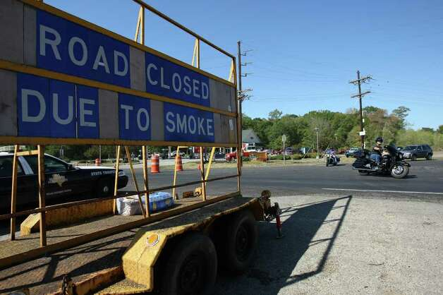 Motorists turn off Wildwood Lane away from FM 1774 which was closed off to due to heavy smoke from wildfires in Grimes County, Saturday in Plantersville. (Eric Christian Smith / For the Chronicle) Photo: Eric Christian Smith, For The Chronicle