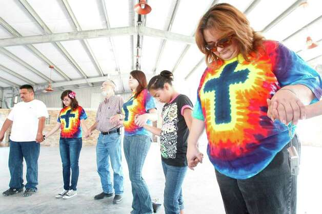 Sylvia Perez prays for fire victims and emergency personnel during a prayer rally at Unity Park on Saturday, Sept. 10, 2011 in Magnolia, TX. Photo: Mayra Beltran, Houston Chronicle / © 2011 Houston Chronicle