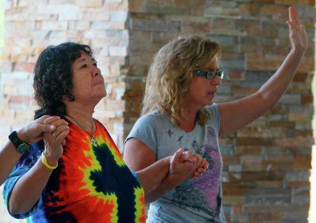 Sister Juanita Martinez and Stephanie Williams pray the Our Father during a prayer rally at Unity Park on Saturday, Sept. 10, 2011 in Magnolia, TX. ( Mayra Beltran / Houston Chronicle ) Photo: Mayra Beltran, Houston Chronicle / © 2011 Houston Chronicle
