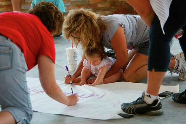 Stephanie Williams and daughter Madylynne Williams write an a appreciation banner to firefighters during a prayer rally at Unity Park on Saturday, Sept. 10, 2011 in Magnolia, TX. (Mayra Beltran / Houston Chronicle) Photo: Mayra Beltran, Houston Chronicle / © 2011 Houston Chronicle