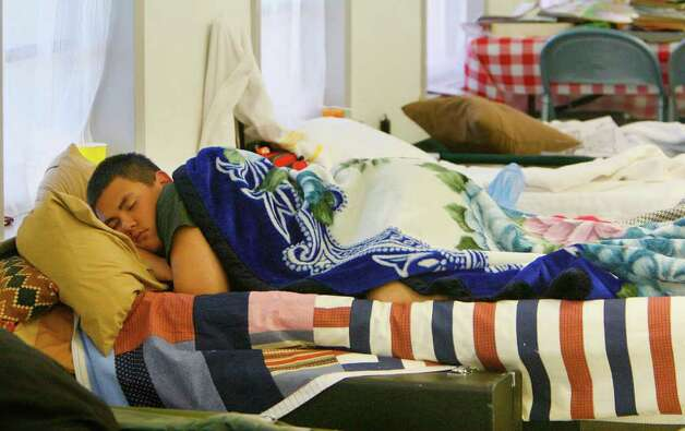 Noe Garza, 15, sleeps in the shelter at the St. John's Lutheran Church where evacuated families are staying due to wildfires on Saturday, Sept. 10, 2011 in Waller, TX. Harada evacuated from the Field Store area in Waller County, and believes her home is untouched by fire. (Mayra Beltran / Houston Chronicle) Photo: Mayra Beltran, Houston Chronicle / © 2011 Houston Chronicle