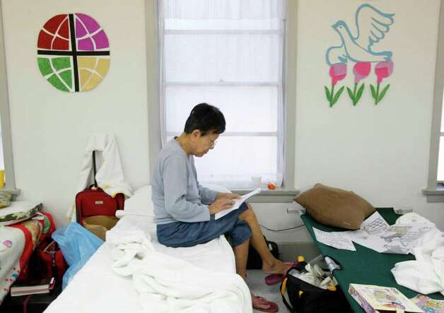 Faye Harada reads at the St. John's Lutheran Church where a shelter is set for evacuated families in Waller County due to wildfires on Saturday, Sept. 10, 2011. Harada evacuated from the Field Store area in Waller County, and believes her home is untouched by fire. Photo: Mayra Beltran, Houston Chronicle / © 2011 Houston Chronicle