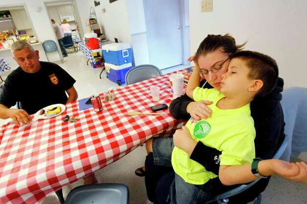 Daniel Lucas, 37, wife Melissa Lucas, 34, and son Brenden Lucas, 5, finish breakfast at the St. John's Lutheran Church where a shelter is provided for evacuated families in Waller County due to wildfires on Saturday, Sept. 10, 2011. The Lucas Family evacuated from the Field Store area in Waller County. Photo: Mayra Beltran, Houston Chronicle / © 2011 Houston Chronicle