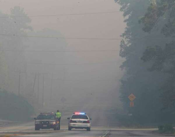 Montgomery County law enforcement officers man a roadblock Friday on FM 1486 because of the heavy smoke drifting in from area wildfires. (Nick de la Torre / Houston Chronicle) Photo: Nick De La Torre / © 2011 Houston Chronicle