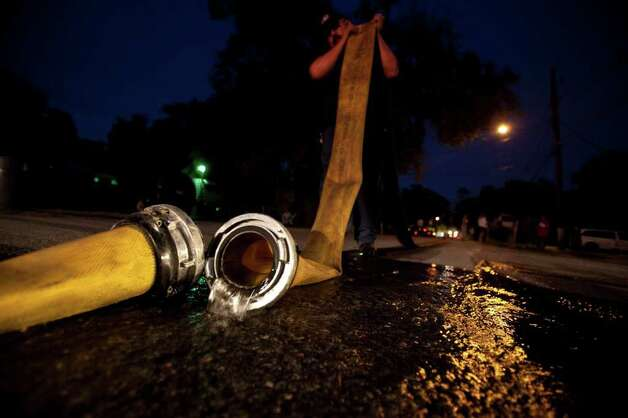 Cloverleaf firefighter Ruben Lopez empties a hose after a fire in a wooded area. Photo: Eric Kayne, For The Chronicle / © 2011 Eric Kayne