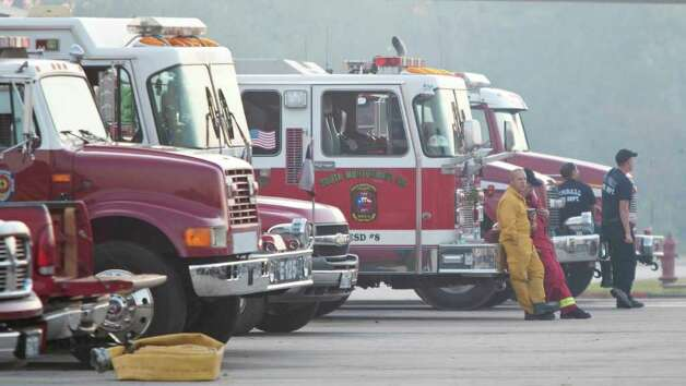 Regional firefighters use the staging area, located at West Magnolia  High School, to engage a wildfire, Friday, Sept. 9, 2011, in Magnolia. Firefighters are still trying to contain the fire that's burned over 12,000 acres in three counties north of the Houston metroplex. Photo: Nick De La Torre, Houston Chronicle / © 2011 Houston Chronicle