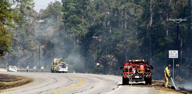 Firefighters put out a fire on F.M. 1488 and Oakhill, Friday, Sept. 9, 2011, in Waller County. Firefighters  are still trying to contain the Riley Road Fire that's burned over 8,000 acres and destroyed 70 homes in Waller County. Photo: Nick De La Torre, Houston Chronicle / © 2011 Houston Chronicle