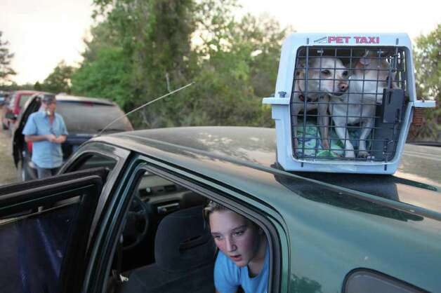 Courtney Hughes sits in the family car as they decide where they will spend the night after residents along Kickapoo Rd. were given a mandatory evacuation in Waller County on Wednesday, Sept. 7, 2011. Photo: Mayra Beltran, Houston Chronicle / © 2011 Houston Chronicle
