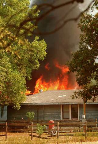 A barn behind a home is on fire south of Todd Mission, Texas Wednesday, Sept. 7, 2011. Magnolia Firefighters fought to save the home and at the time the photographer left the scene the home was still unharmed by the blaze. Photo: Mayra Beltran, Houston Chronicle / © 2011 Houston Chronicle