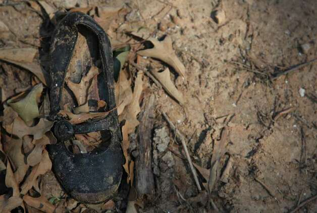 A little girls shoes were found near a home consumed by the fire in the Ranch Crest subdivision near Magnolia. Photo: Mayra Beltran, Houston Chronicle / © 2011 Houston Chronicle