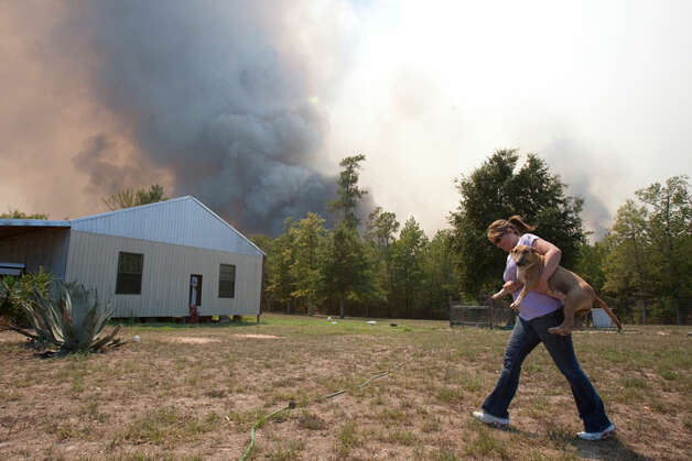Charlotte Rudle takes one of her dogs to her vehicle as she  evacuates from her home as a wild fire changes direction, Tuesday, Sept. 6,  2011, in Montgomery County. ( Nick de la Torre / Houston Chronicle )