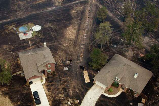 Charred ground surrounds two homes spared by a wildfire on N. Nueces Trail in the Ranch Crest subdivision on Tuesday, Sept. 6, 2011, near Magnolia, Texas. Some 20 homes have burned in the fire; 150 are immediately threatened; and 100 more are in the blaze's path, according to Texas Forest Service officials. Photo: Smiley N. Pool, Houston Chronicle / © 2011  Houston Chronicle
