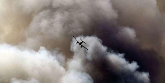 Planes drop fire retardant on wildfires in the Bastrop area Monday. (JOHN DAVENPORT/San Antonio Express-News) Photo: SAN ANTONIO EXPRESS-NEWS