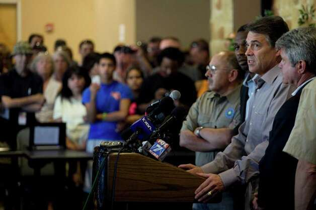 Gov. Rick Perry, center, holds a news conference to discuss wild fires in central Texas, Monday, Sept. 5, 2011, in Bastrop, Texas.  A roaring wildfire raced unchecked Monday through rain-starved farm and ranchland in Texas, destroying nearly 500 homes during a rapid advance fanned in part by howling winds from the remnants of Tropical Storm Lee.   (AP Photo/The Daily Texan, Tamir Kalifa) Photo: Tamir Kalifa, Associated Press / The Daily Texan