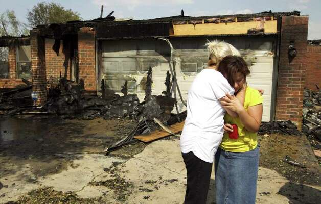 Virginia Esquivel, right, is comforted by her neighbor, Yolanda Rodriguez, after Esquivel's home in Cedar Park, Texas, burned on Sunday, Sept. 4, 2011.  Two homes on the street were destroyed by the fire. (AP Photo/Austin American-Statesman, Jay Janner)  MAGS OUT; NO SALES; TV OUT; INTERNET OUT; AP MEMBERS ONLY Photo: Jay Janner, MBR / Austin American-Statesman